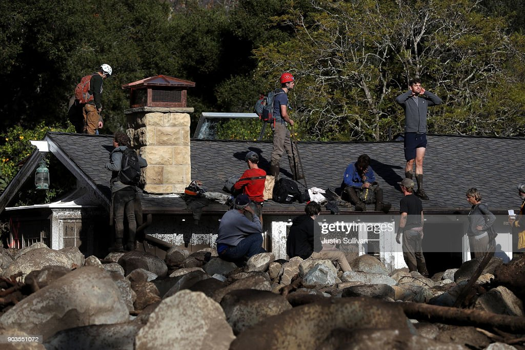 Residents stand on a home that was destroyed by a mudslide on January 10, 2018 in Montecito, California. 15 people have died and hundreds are still stranded after massive mudslides crashed through Montecito, California early Tuesday morning.
