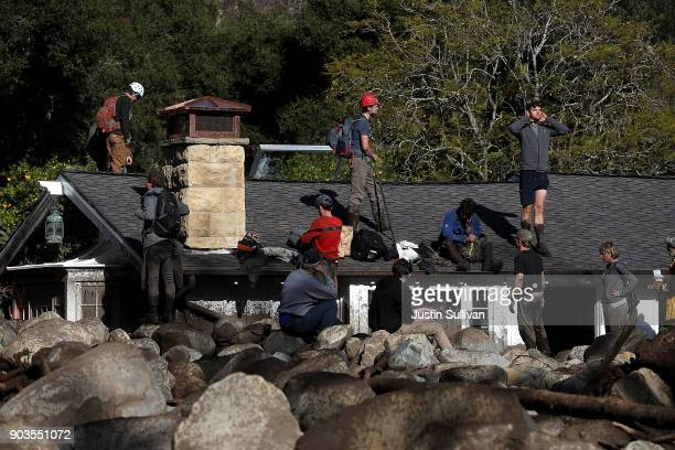 Residents stand on a home that was destroyed by a mudslide on January 10 2018 in Montecito California 15 people have died and hundreds are still...