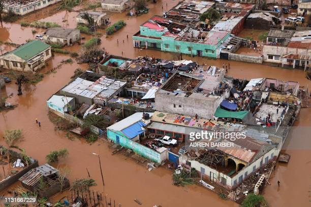 TOPSHOT Residents stand on rooftops in a flooded area of Buzi central Mozambique on March 20 after the passage of cyclone Idai International aid...