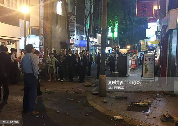 Residents stand on the street following an earthquake in Kumamoto city on April 14 2016 The strong 64magnitude earthquake struck at 926 pm in...