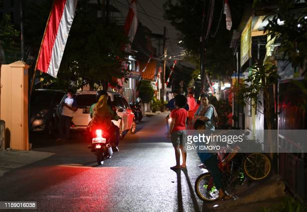 Residents stand outside in the street after a strong earthquake hit the area around Jakarta on August 2 2019 A powerful earthquake struck off the...