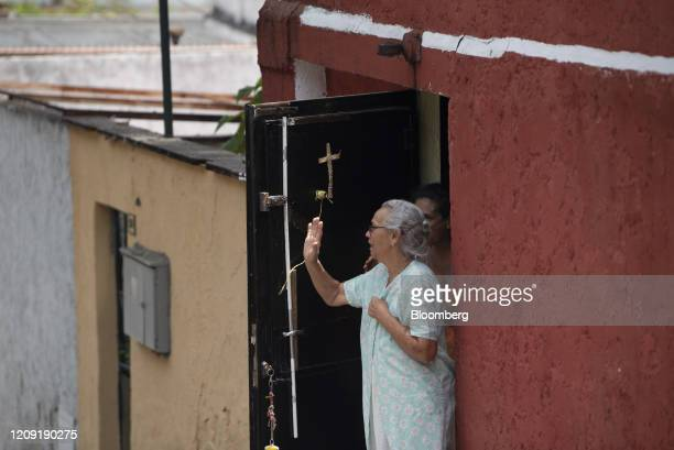 Residents stand outside of a home as a priest delivers blessings from a vehicle during Palm Sunday in Caracas Venezuela on Sunday April 5 2020 Amid...