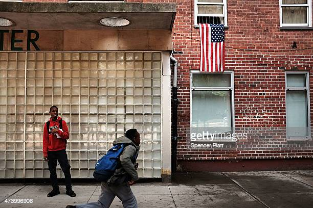 Residents stand outside of an East Harlem public housing complex on May 19 2015 in New York City New York City Mayor Bill de Blasio announced his...
