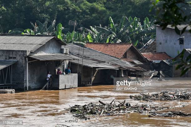 Residents stay on the second floor of their house amid floodwaters in Jakarta on April 26 after several areas were affected by heavy rainfall