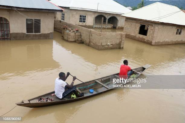 Residents steer a dugout canoe past flooded houses following heavy rain in the Nigerian town of Lokoja in Kogi State on September 14 2018