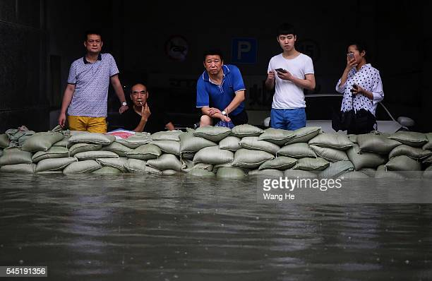 Residents stood in the sandbag on a flooded street in heavy rain in Wuhan £¬Hubei province China6 July 2016 An overnight storm following days of rain...