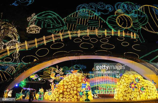 Residents stroll through a park illuminated with Christmas lights on December 2 2008 in Medellin AFP PHOTO/Raul Arboleda