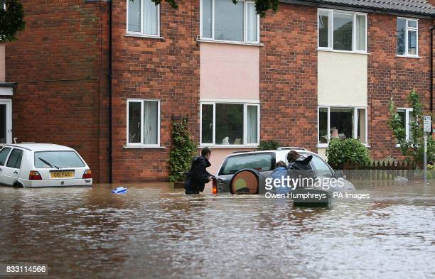 Residents struggle to move their car in Beverley North East Yorkshire after heavy rainfall caused flooding