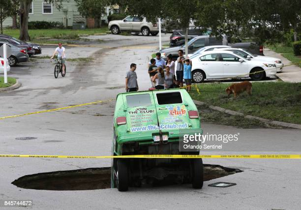 Residents survey the scene of a van in a sinkhole on Monday Sept 11 that opened up at the Astor Park apartment complex in Winter Springs Fla during...