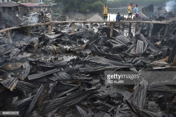Residents survey their destroyed homes after a fire hit at an informal settlers area along the coast in Bacoor town Cavite province southwest of...