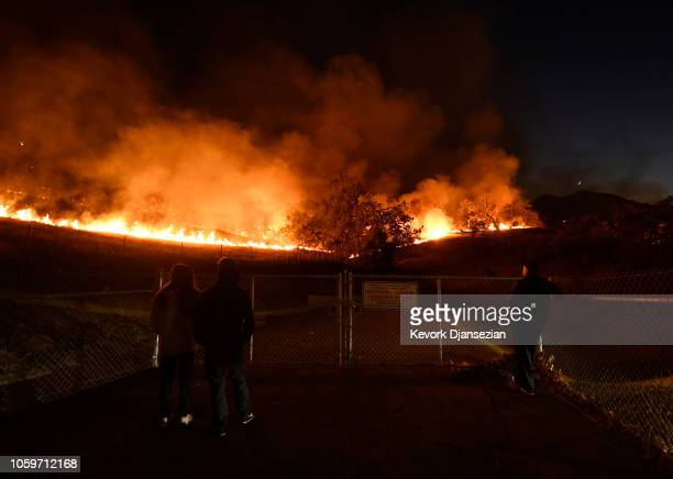 Residents take a look at the Woolsey Fire burning brush and trees on November 9 2018 in Agoura Hills California About 75000 homes have been evacuated...