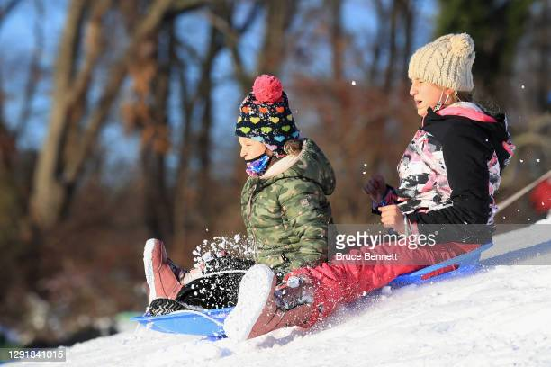 Residents take advantage of the small hills and the recent snowfall to sled at Mattlin Middle School on December 17, 2020 in Plainview, New York. The...