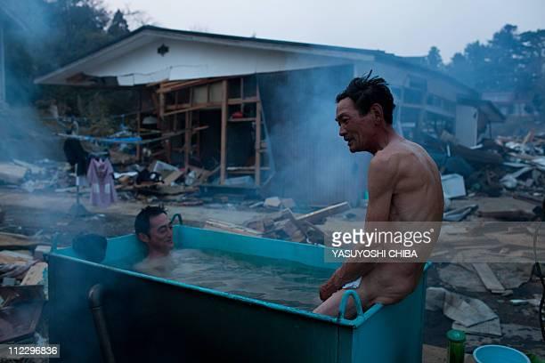 Residents take an out door bath amongst tsunami devastation in Kesennuma city Miyagi prefecture on April 14 2011 Japan's seismologists were so...