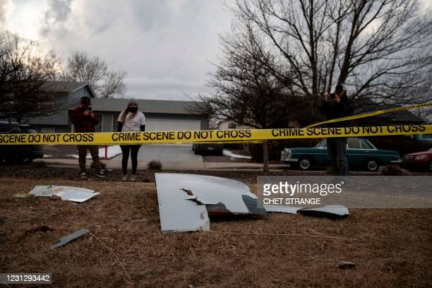 Residents take pictures of debris fallen from a United Airlines airplane's engine on the neighborhood of Broomfield, outside Denver, Colorado, on...