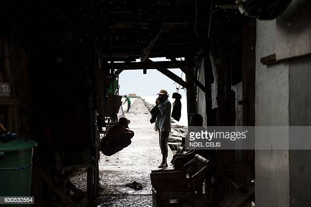 Residents take shelter at houses constructed on the breakwater in Baseco Manila on December 26 2016 Typhoon NockTen which made landfall on the...