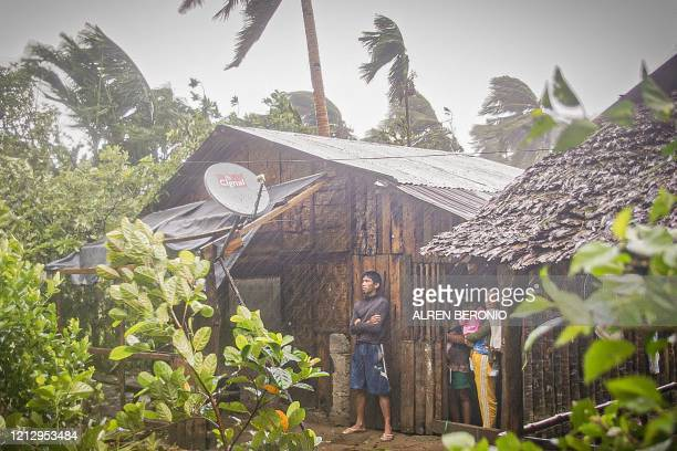 Residents take shelter by their house as they observe rain and wind in Canavid town Eastern Samar province central Philippines on May 14 as Typhoon...