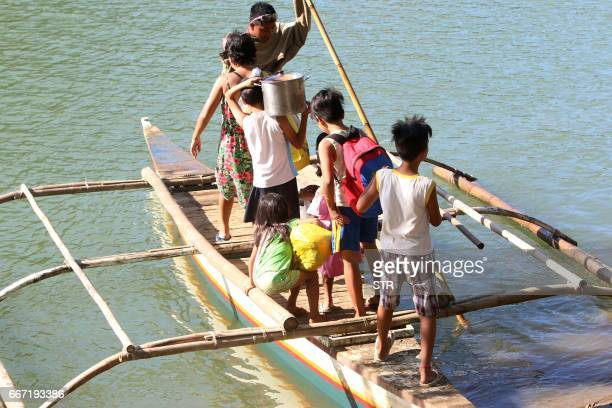 Residents take their belongings as they ride on a wooden boat to a safer place in the village of Napo Inabanga town Bohol province in the central...