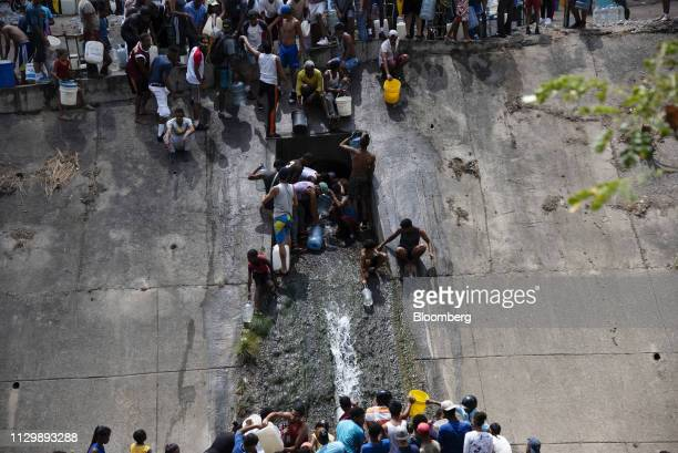 Residents take water from a drainage pipe in the Guaire river in the San Agustin neighborhood of Caracas Venezuela on Monday March 11 2019 Caracas...