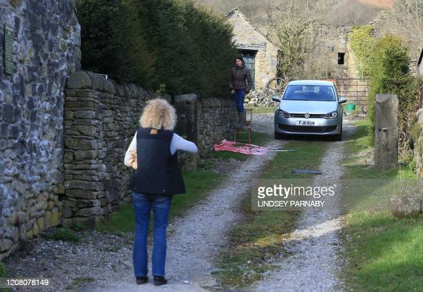 Residents talk as they observe social distancing on government advice in the village of Eyam in Derbyshire northern England on March 23 2020 In the...