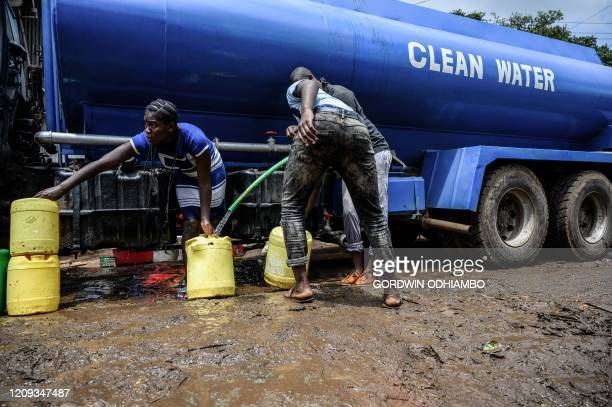Residents tend to their jerrycan as they fill them with free water distributed by the Kenyan government at Kibera slum in Nairobi Kenya on April 7...