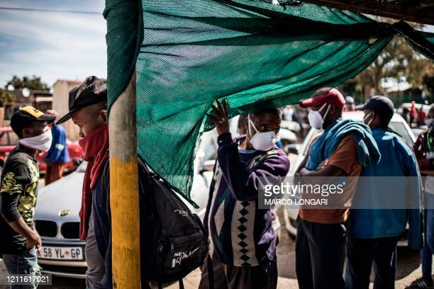 Residents the Olievenhoutbosch township in Centurion, queue on May 2, 2020 during a food distribution organised by the South African non profit...