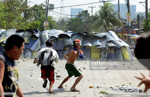 Residents throw stones and bottles at policemen during a demolition operation in a squatters area in Manila on January 27 2014 The government wants...