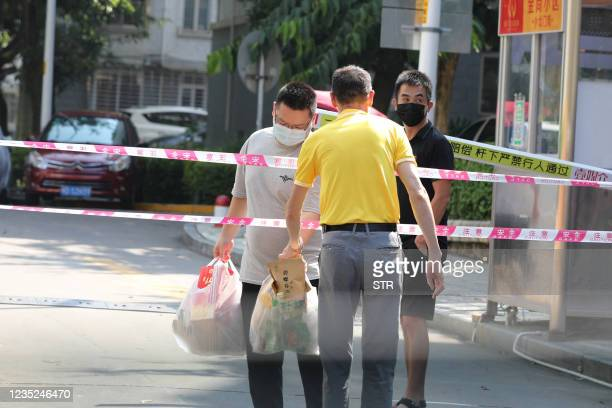 Residents transfer daily necessities at a residential area under tight restrictions due to cases of the Covid-19 virus in Xiamen in China's eastern...