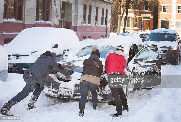 Residents try to free a stranded car after it became stuck in snow on February 2 2015 in Chicago Illinois Snow began falling in the city Sunday...