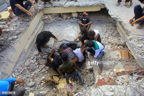 Residents try to rescue a man trapped under the rubble of a twostorey shop after it collapsed during an earthquake in Pidie Jaya Aceh province on...