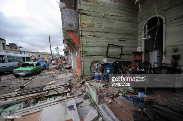 Residents try to salvage belongings from their destroyed homes after the passage of a tornado in Havana on January 28 2019 A rare and powerful...