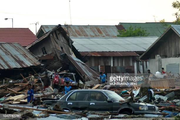 TOPSHOT Residents trying to salvage belongings from their homes which collapsed after an earthquake and tsunami hit Palu on Sulawesi island on...