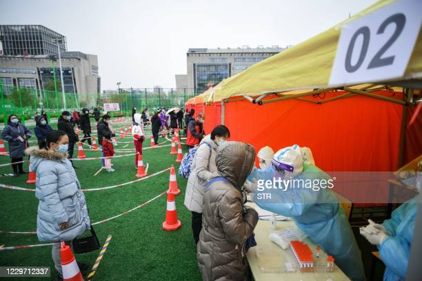 Residents undergo Covid-19 coronavirus tests at a makeshift testing center in Tianjin on November 21 after new coronavirus cases were detected in the...
