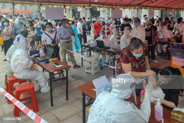 Residents undergo nucleic acid tests for the Covid-19 coronavirus in Xiamen, in China's eastern Fujian province on September 14, 2021. - China OUT /...