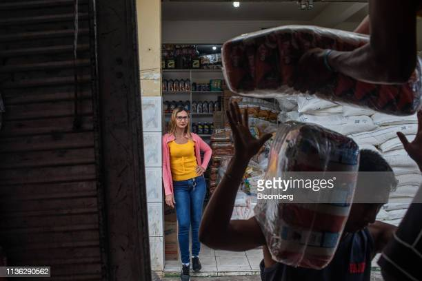 Residents unload food from a truck near the Venezuelan border in Pacaraima, Brazil, on Wednesday, April 10, 2019. Venezuelan refugees looking for...