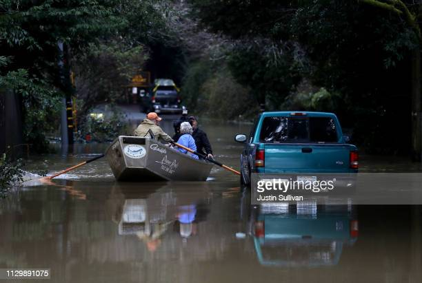 Residents use a boat to navigate floodwaters on February 15 2019 in Guerneville California An atmospheric river a narrow corridor of concentrated...