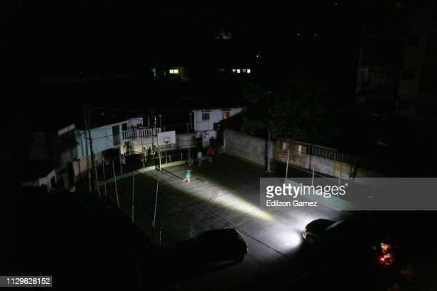 Residents use a car's headlamps as a source of light after a nationwide blackout occurred March 10, 2019 in Caracas, Venezuela. Over seventy percent...
