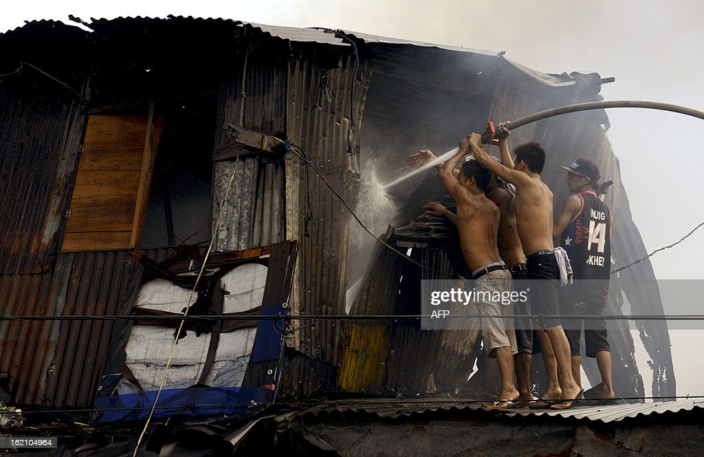 Residents use a firemen's hose to extinguish a fire that engulfed a slum area in Manila on February 19, 2013. Almost 100 houses were destroyed, leaving 200 residents homeless, with three bodies found according to a local media report.