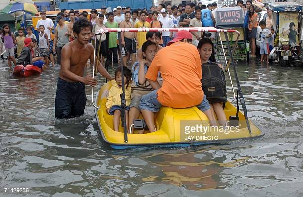 Residents use a hired pedal boat to get around in the flooded streets of the Malabon north of Manila 13 July 2006 following heavy rains brought by...