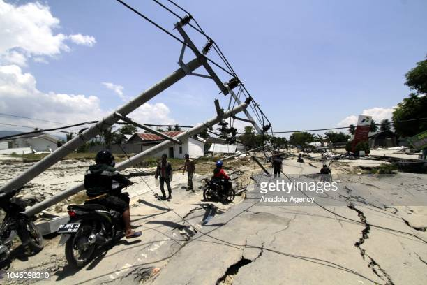 Residents use a motorcycle on the Poros road after it was damaged following an 7.7-magnitude earthquake in Palu, Central Sulawesi, Indonesia on...