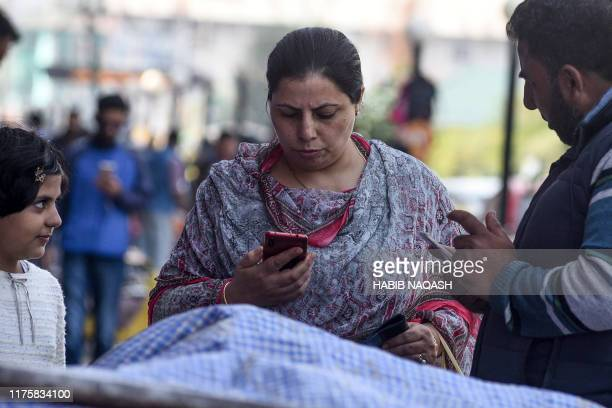 Residents use mobiles phones in Srinagar on October 14 following Indian government's decision to restore mobile phones network in Indianadministered...