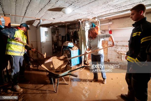 Residents use shovels to clear their basement of mud after flooding in the Slovenian village of Jelendol on October 30 2018