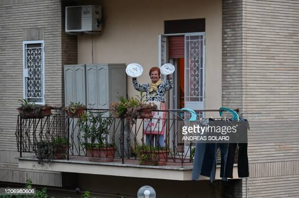 A residents uses pot lids to play cymbals as she takes part in a music flash mob called Look out from the window Rome mine aimed at liven up the...