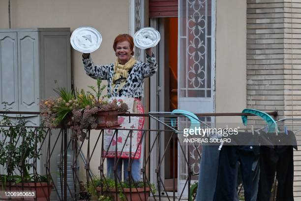 TOPSHOT A residents uses pot lids to play cymbals as she takes part in a music flash mob called Look out from the window Rome mine aimed at liven up...