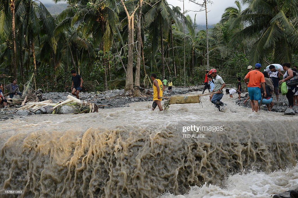 Residents using a makeshift stretcher carry the dead body of a boy as they cross a destroyed highway in the village of Andap, New Bataan town, Compostela Valley province on December 5, 2012, one day after Typhoon Bopha hit the province. The death toll from a typhoon that ravaged the Philippines jumped to 238 on December 5 with hundreds missing, as rescuers battled to reach areas cut off by floods and mudslides.