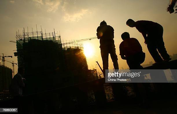 Residents view a construction site on sunset September 19 2007 in Chongqing Municipality China China's property investment rose 29 per cent up from...