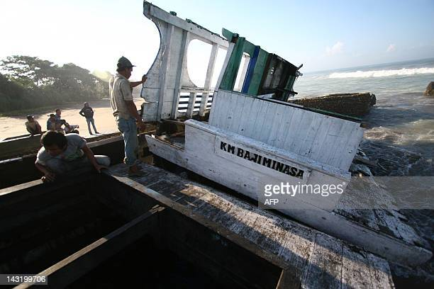 Residents view the asylum seekers boat wreckage on the shore of Wonogoro village in East Java province on April 21, 2012. Indonesian authorities were...