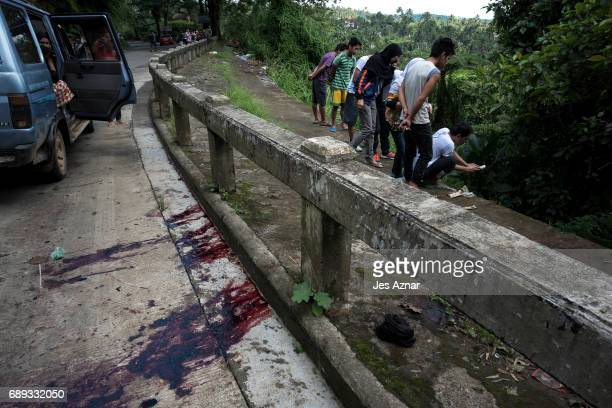 Residents view unidentified bodies believed to be executed by armed militants and dumped in a ditch as blood stains are seen on the pavement of a...
