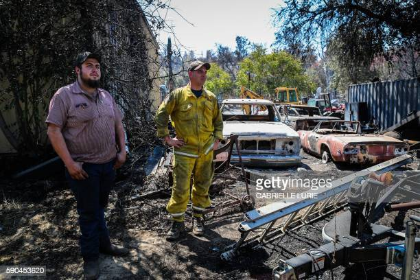 Residents Wade Holley and Mike Boyce look over the damage to their cars in the Clayton Fire at the Clearlake machine shop in Lower Lake California...