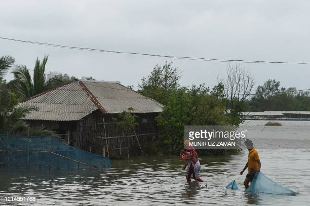 Residents wade through a flooded area after a dam broke following the landfall of cyclone Amphan in Shyamnagar on May 21 2020 At least 84 people died...