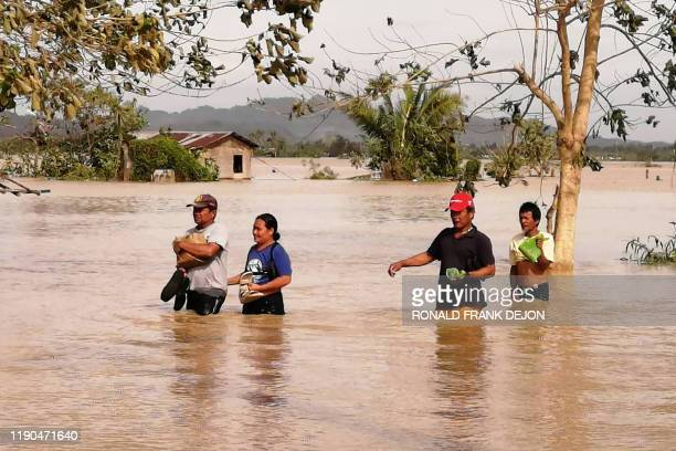 Residents wade through a flooded highway, caused by heavy rains due to typhoon Phanfone, in Ormoc City, Leyte province in central Philippines on...